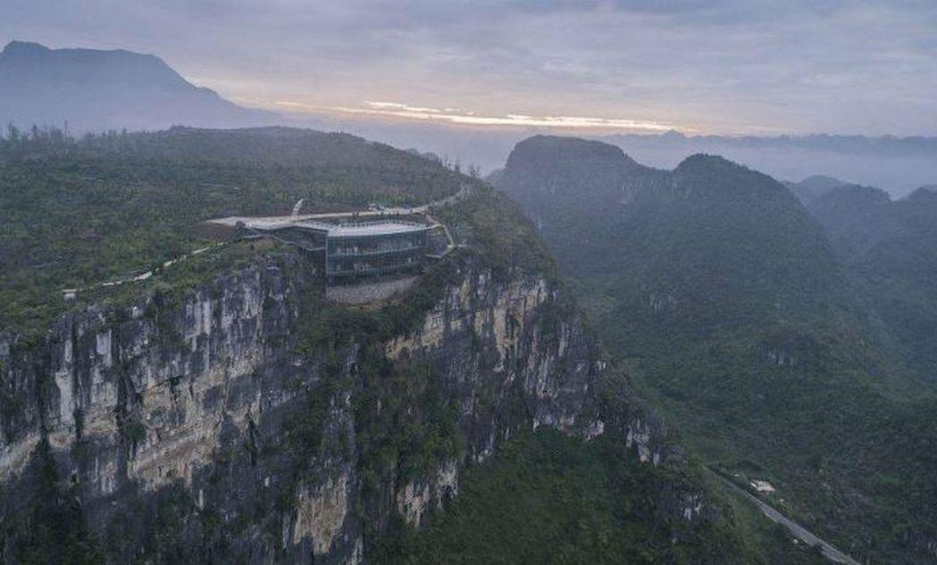 貴州溶岩美術館造型如一輪彎月、玻璃幕牆,嵌入約165米高懸崖的自然凹槽內,遠遠望...