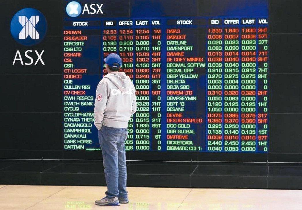 投資人站在顯示螢幕前觀看澳洲證交所股票行情波動的檔案照。 路透