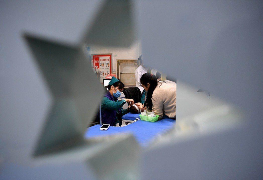 鄭州市兒童醫院輸液大廳,醫務人員在為患兒輸液。 新華社資料照片