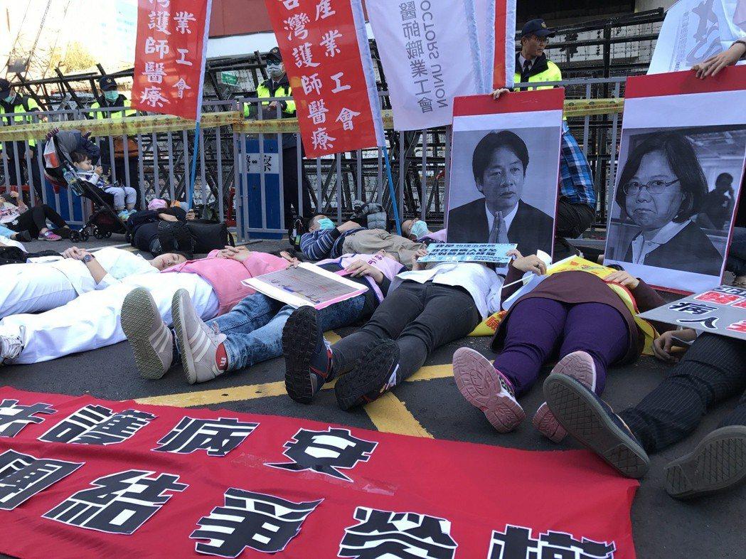 圖為去年12月23日勞基法反修法抗議大遊行前,醫護人員工會在立院外躺臥,表達修法...