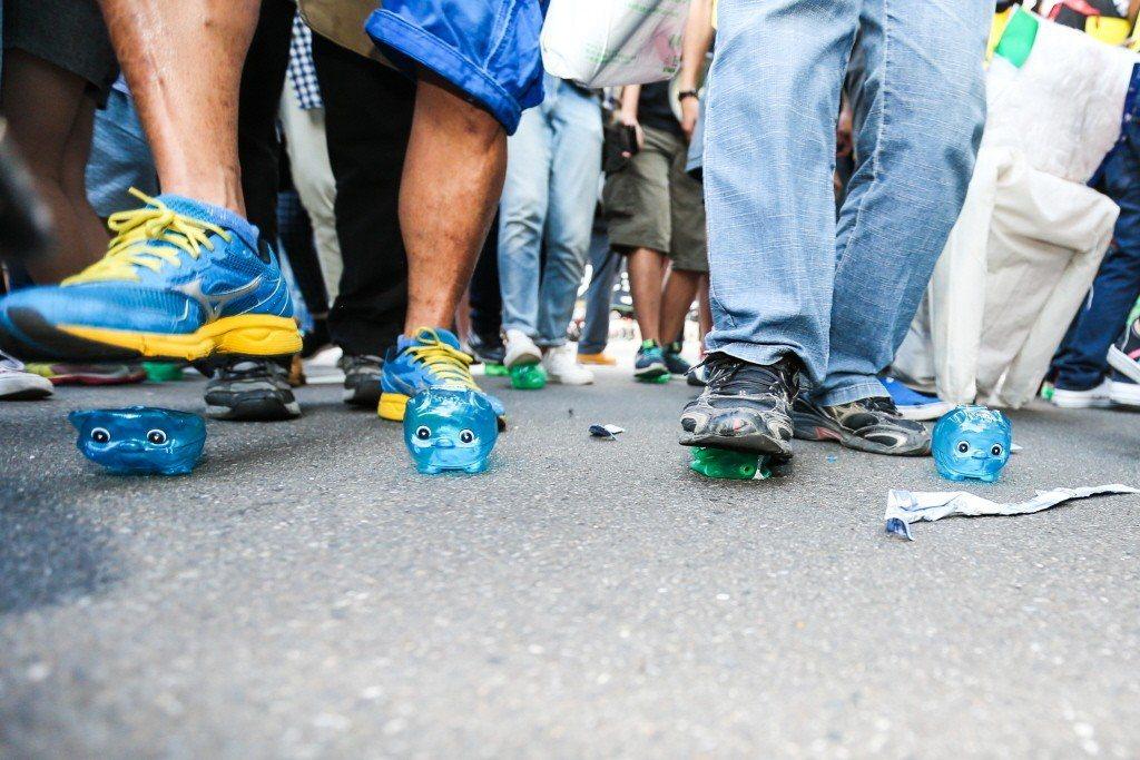 圖為2015年「秋鬥」遊行,遊行民眾把手中的小豬撲滿踩扁,表達對藍綠的不滿。 圖...