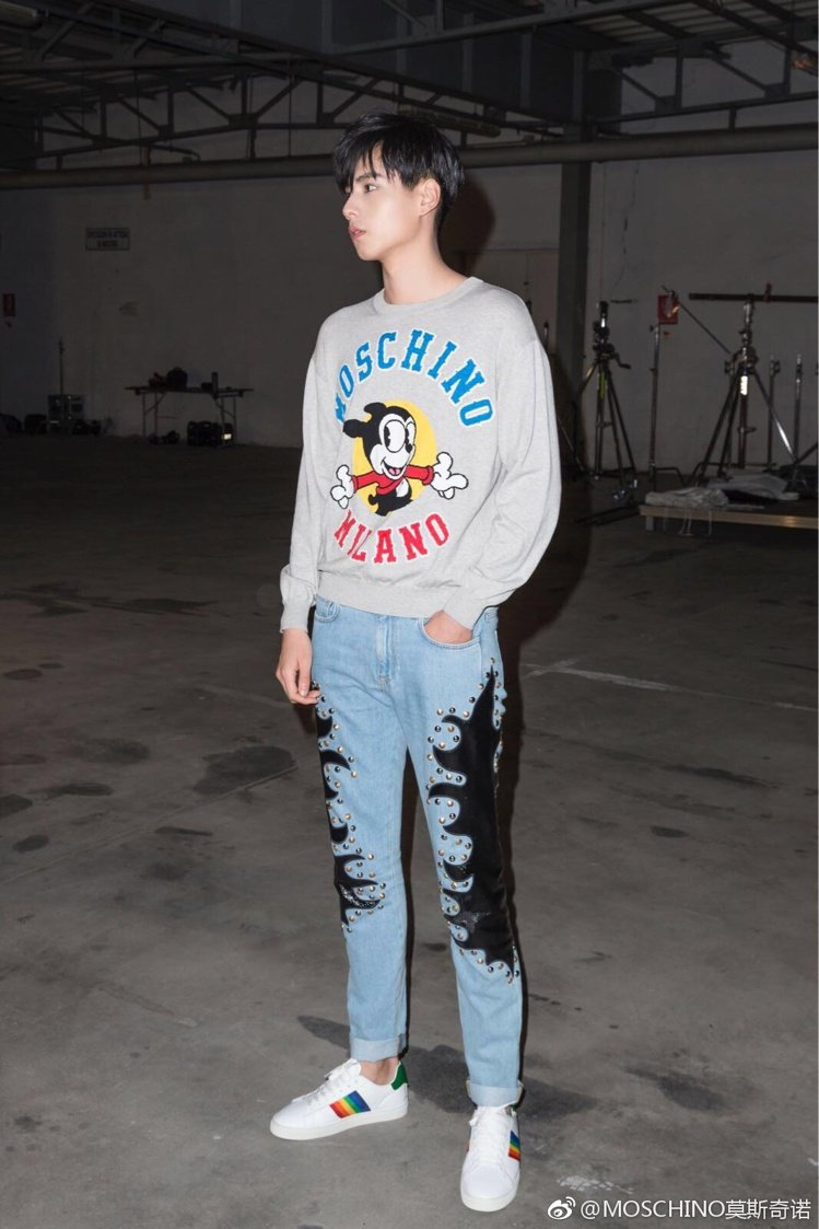 胡一天現身Moschino服裝秀時,則是換上帶有卡通圖案的大學T恤和皮革拼接牛仔...