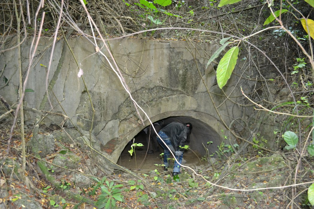 原本約3公尺高的戰備水庫入口,泥沙淤塞目前只剩約1公尺,必須屈身進入。圖/舊城文...
