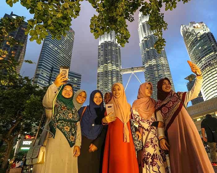 馬來西亞著名的雙子星大樓前,一群當地消費者開心拿著智慧型手機自拍。這幾年東南亞六...