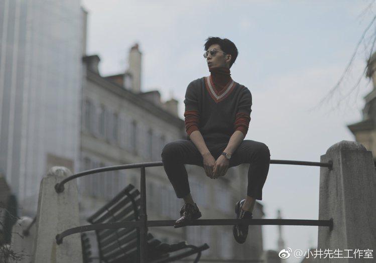 井柏然以日内瓦街头为背景,身穿绲红边针织V领毛衣,内搭高领套头T恤,加上深灰色长...