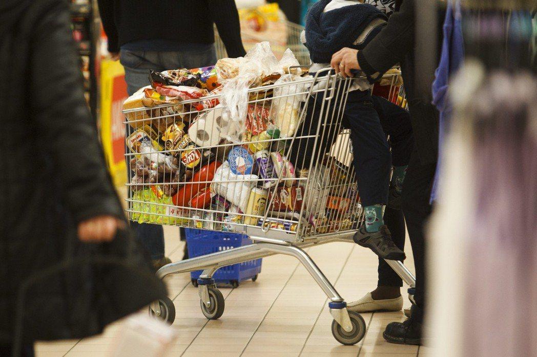 暴滿的購物車中,是現代人追求便利的飲食選擇,但這個代價就是週週爆表的帳單。 圖/...