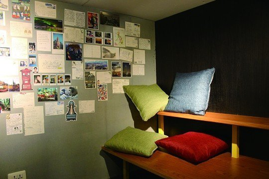 紅米青旅大廳一角的休息區,牆壁上貼滿旅客寄送給員工的明信片。(攝影 /蔡敏姿)