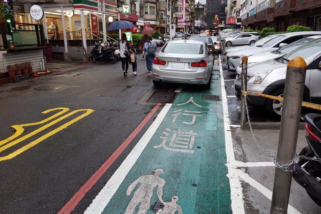 現況下的標線型人行道,少了硬體阻隔設施,無法阻擋汽機車入侵與停放。 圖/聯合報系...