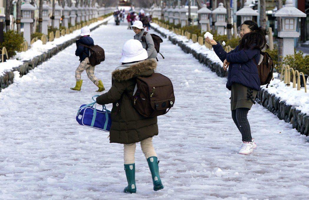 日本東京下大雪,圖為孩童放學後在街上玩雪情形,非新聞當事人。 美聯社