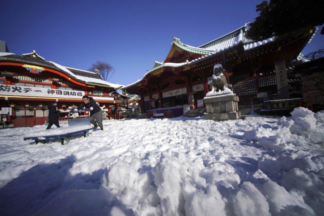 一名男子23日在東京神田神社清理積雪。 美聯社