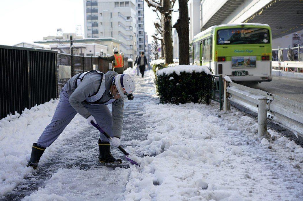 東京一夜大雪造成交通大亂,23日交通運輸人員忙著剷20多公分厚的積雪。 歐新社