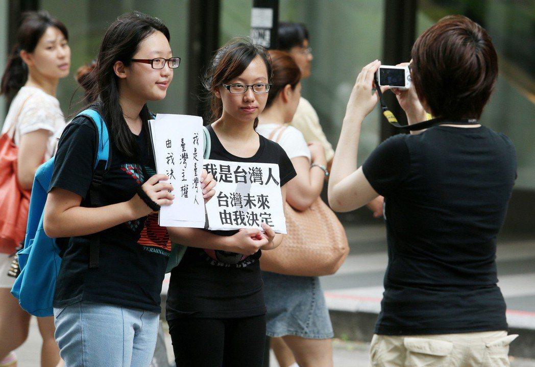 國台辦主任張志軍訪台,一群年輕人在台北東區街頭號召路過民眾拿著「台灣未來由我決定...