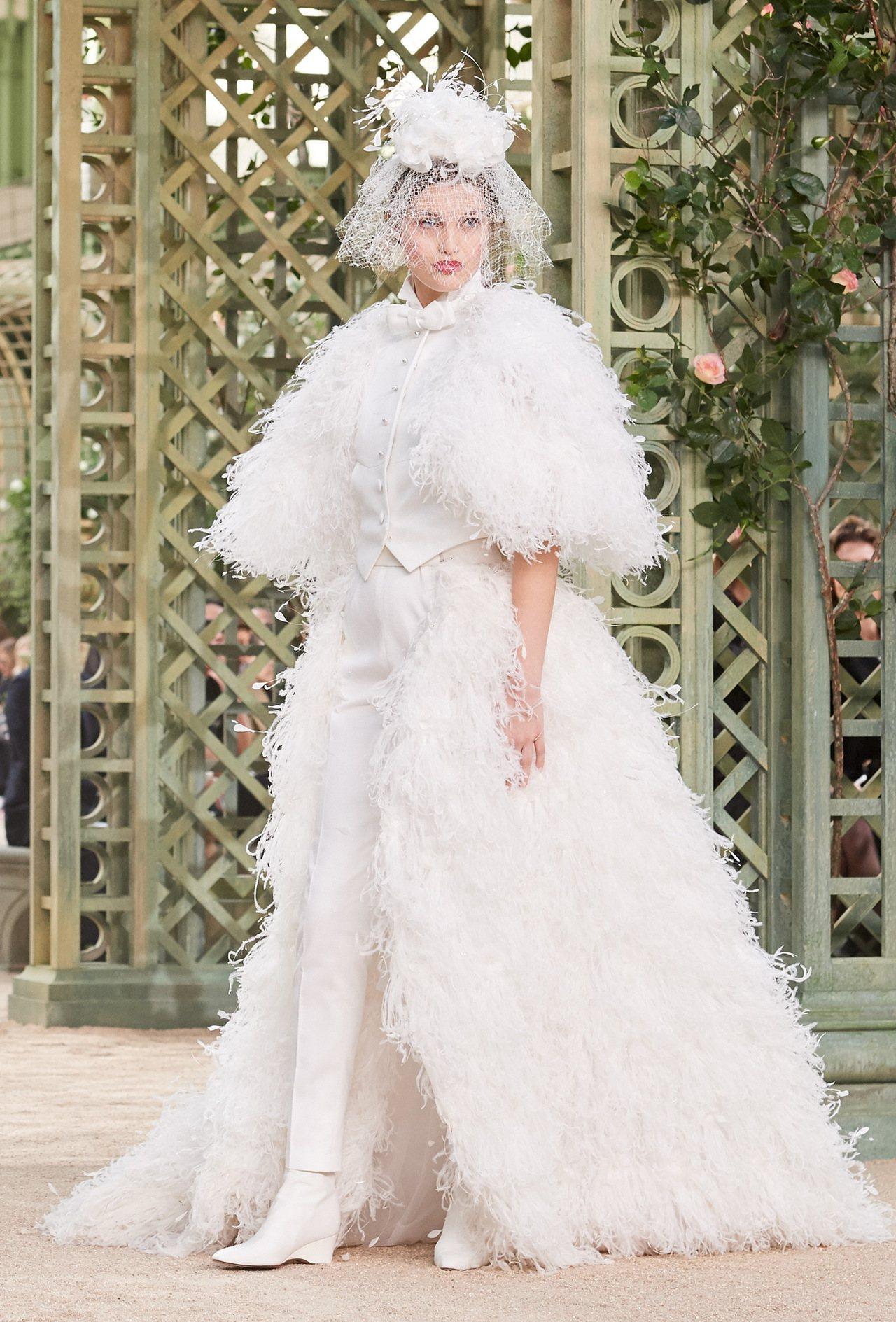 壓軸登場的一件純白禮服則是顛覆傳統,運用西裝背心搭長褲的方式,結合羽毛裙襬,完美...