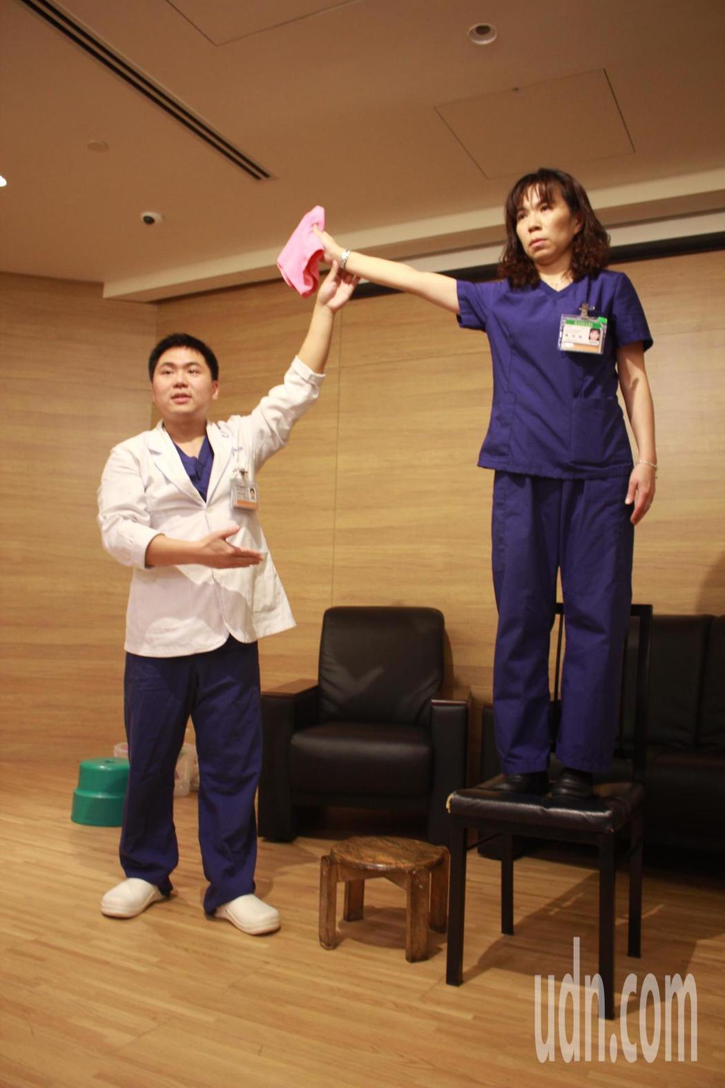 亞東醫院復健科物理治療師林文豪(左)、陳怡伶(右),示範「以凳代踮」的正確大掃除...