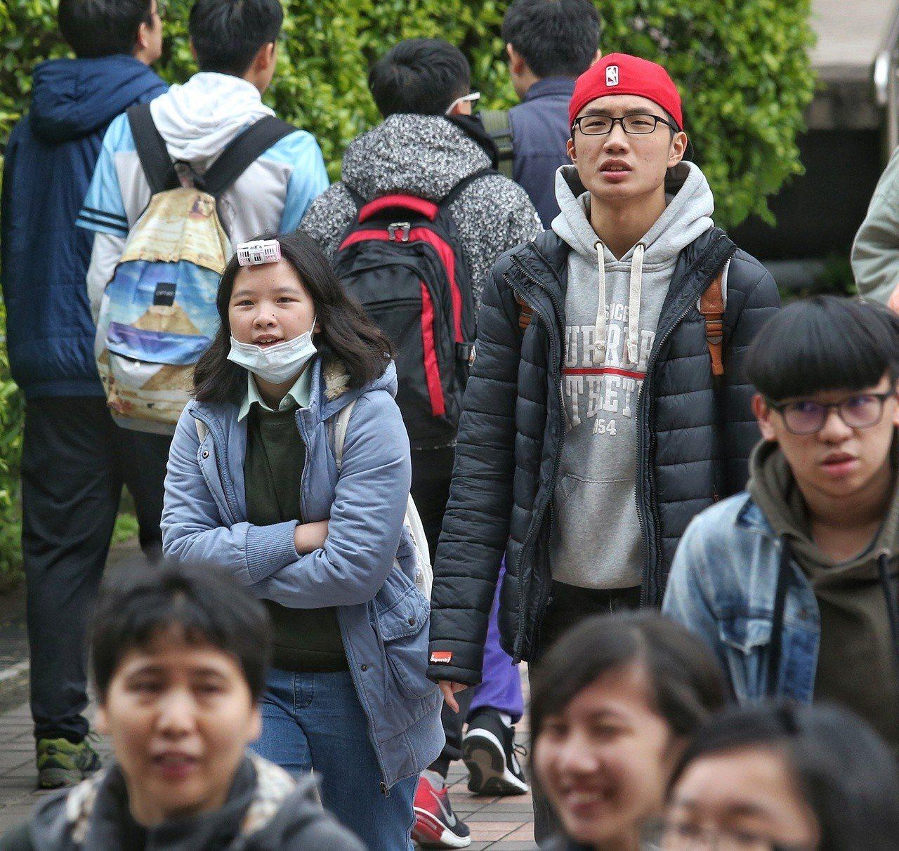 107年學測考生戴著口罩穿著厚外套,寒風中拚金榜。聯合報系記者鄭清元/攝影
