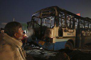 印度哈里亞納邦的一名司機24日看著被反對「帕德瑪瓦特」暴民縱火的大客車。 美聯社