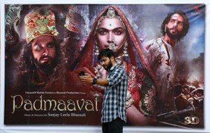 一名男子25日在印度科契市與電影院外的「帕德瑪瓦特」海報自拍。 路透