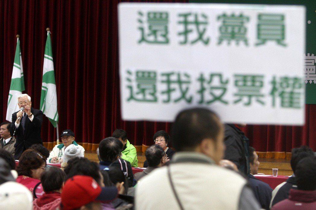民進黨中央2011年決定以「全民調」作為總統與區域立委提名方式,有黨員拿著海報,...