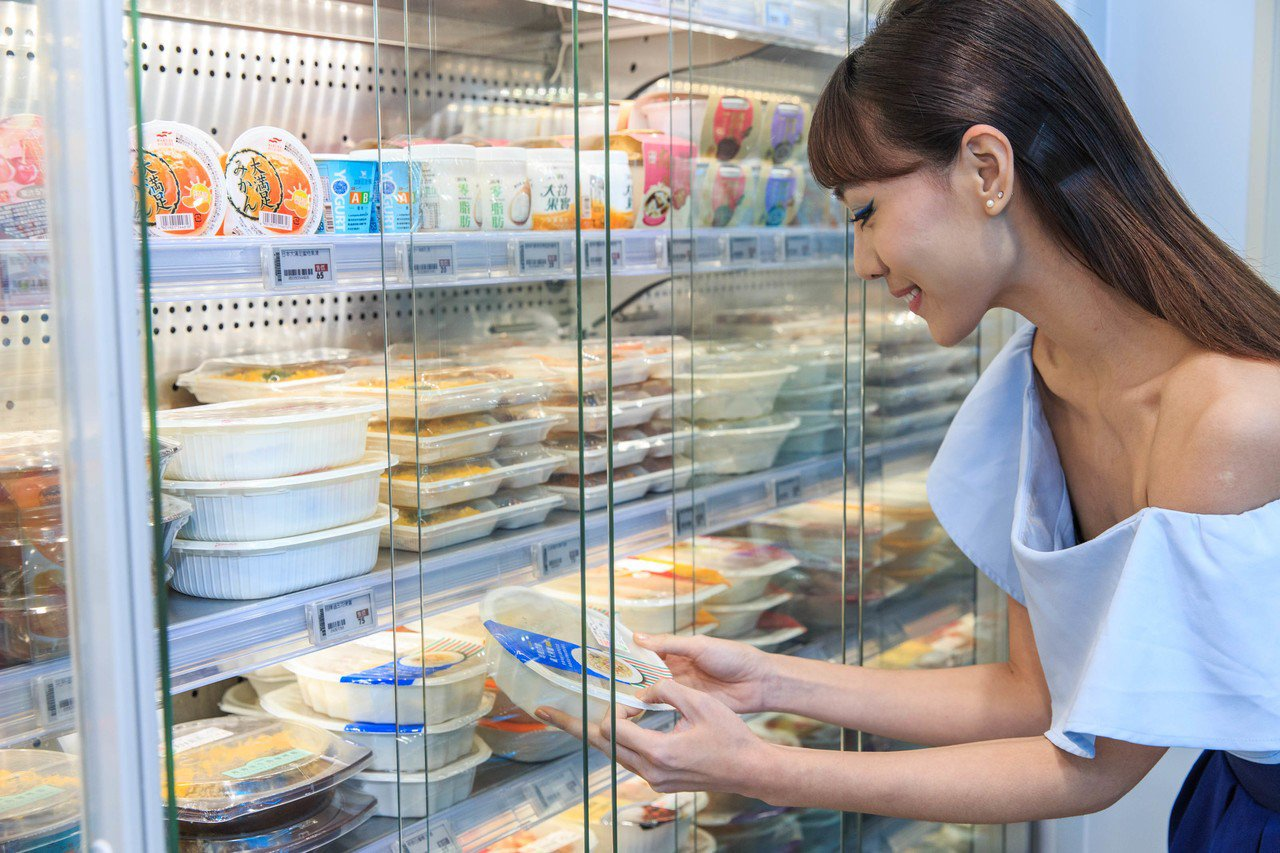 消費者於感應式自動門冰箱前挑選鮮食相關商品。 圖/統一超商提供