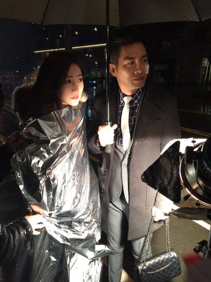 曾莞婷(左)與謝承均(右)撐著傘在燈光前取暖。 圖/擷自曾莞婷臉書