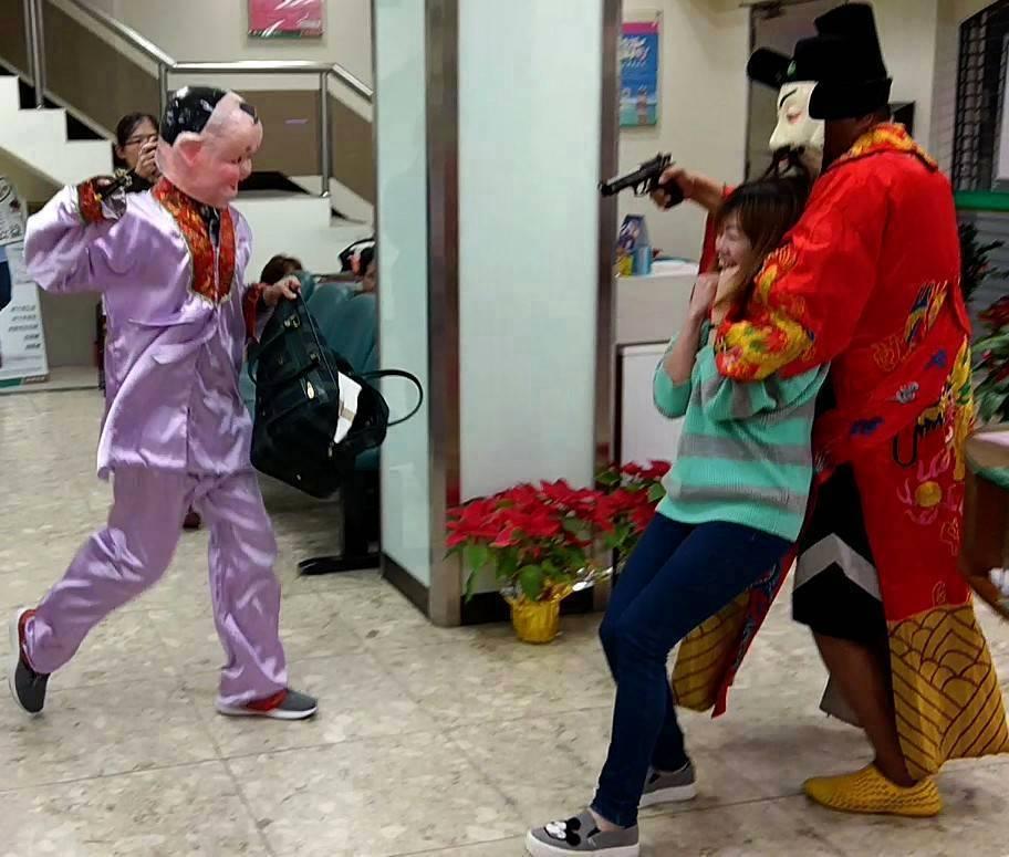 年節將近,台北市信義警分局舉行防搶演練,由員警演出歹徒,模擬持槍搶銀行,還打扮為...