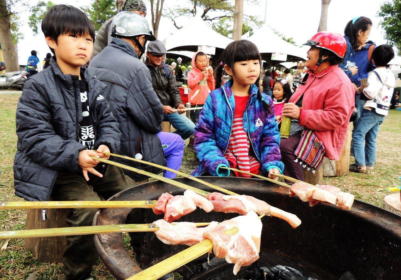 2018台東第一場慢食節活動昨登場,不少遊客開心的自己動手體驗原住民烤豬肉。 記...