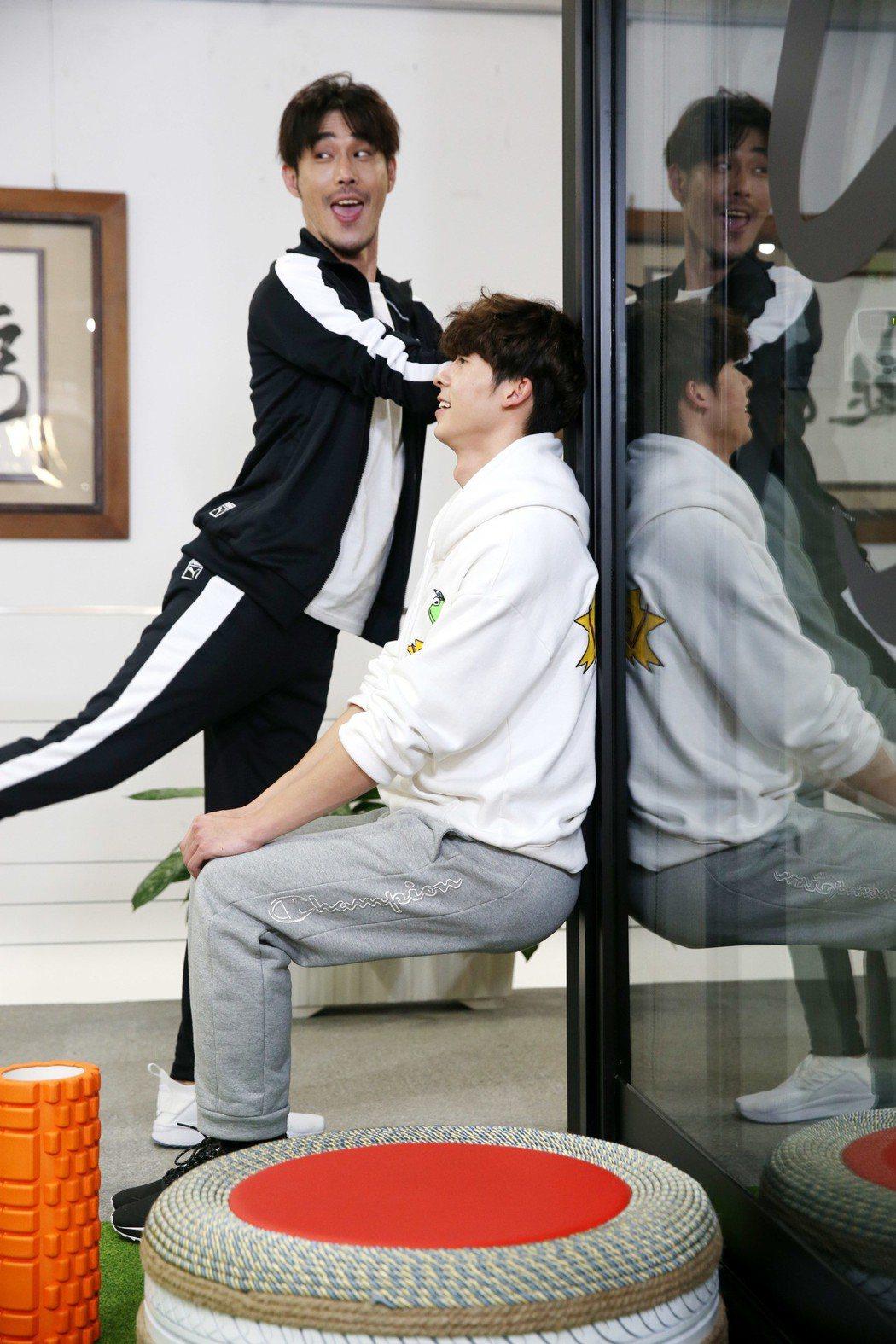 黃騰浩(後)、許光漢(前)示範居家健身,深蹲練肌力。記者邱德祥/攝影