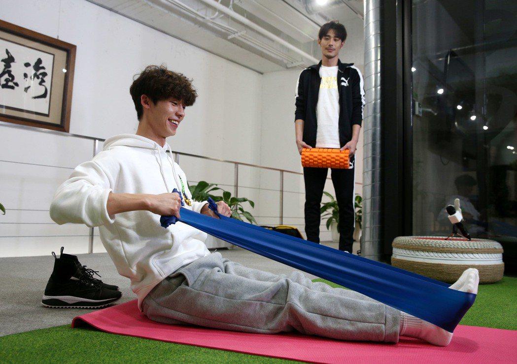 黃騰浩(後)、許光漢(前)示範居家健身,使用彈力帶。記者邱德祥/攝影