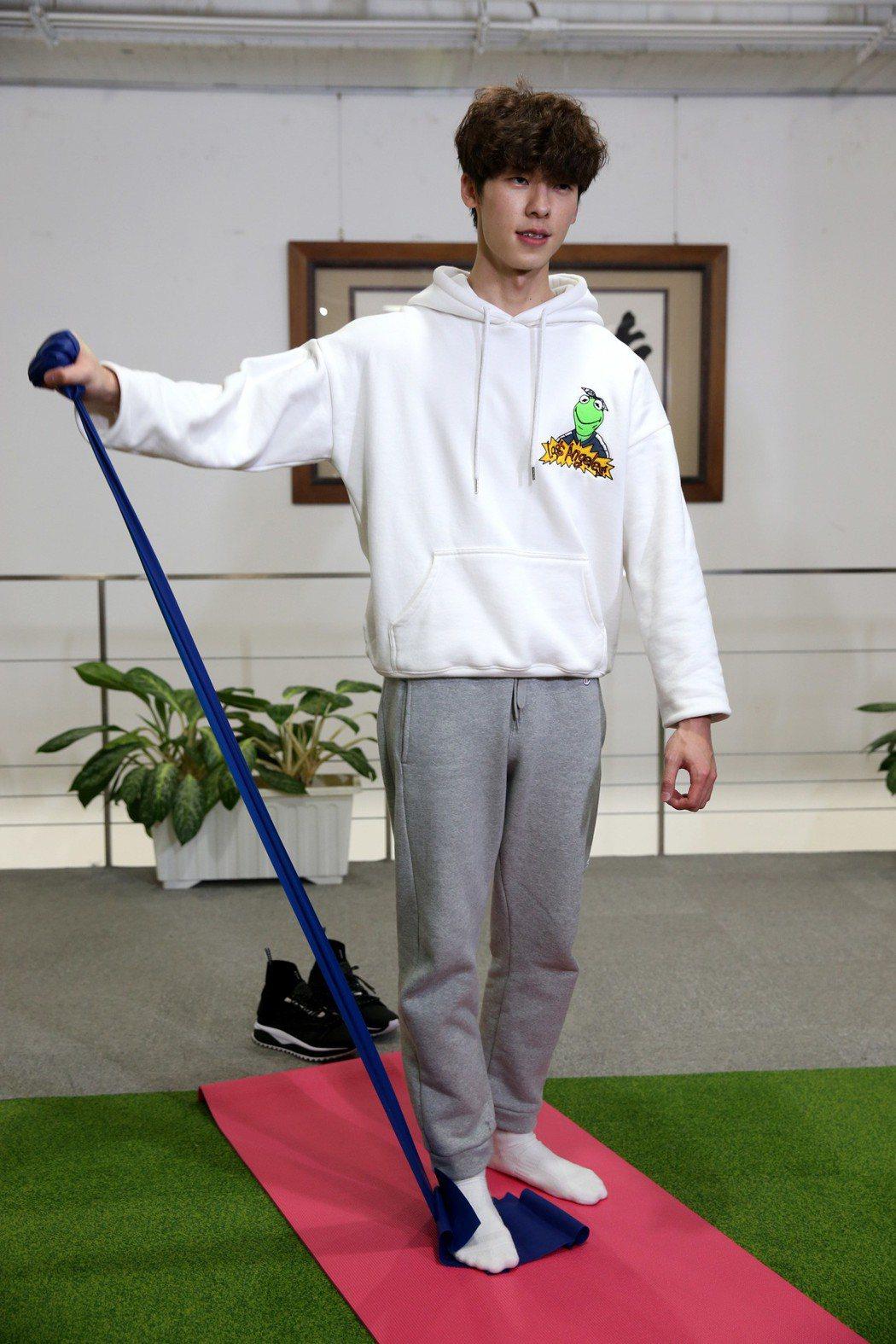 許光漢示範居家健身,使用彈力帶。記者邱德祥/攝影