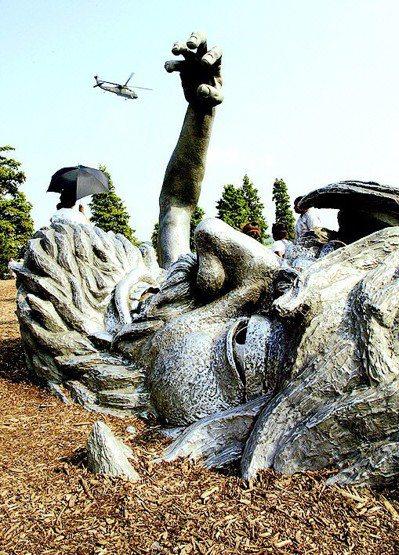 一架美軍「黑鷹」直升機從華盛頓DC的「覺醒」雕像上空掠過,構成圖中這幅巨人「伸手...