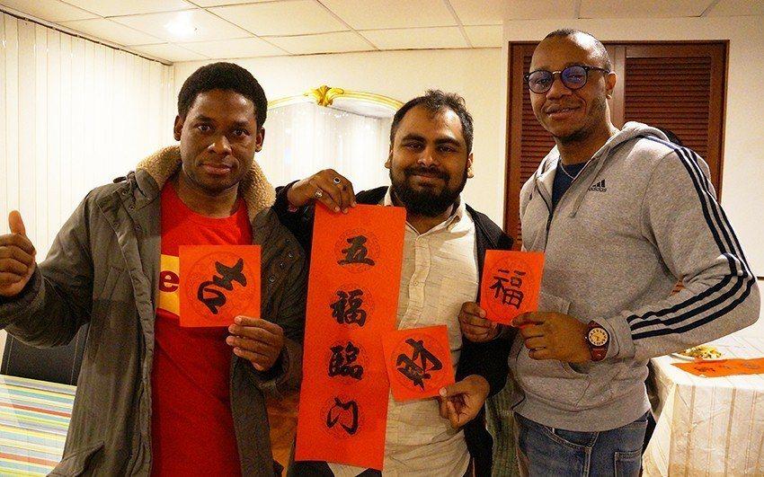 來自印度的芭納利(中)、來自海地的利馬諾(左)及杜明(右)在春節聚餐活動中體驗傳...
