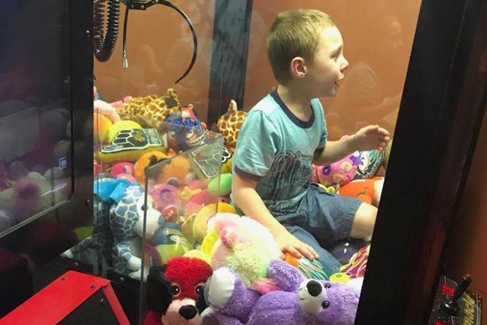 美國佛羅里達州一名男孩爬進抓娃娃機想拿填充玩具,結果被困在裡面出不來。佛州泰特斯...