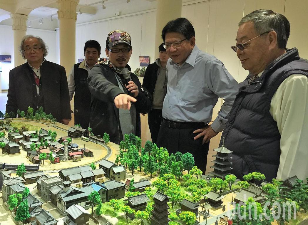 作詞人方文山(左2)正向屏東縣長潘孟安等人解說自己的作品「精靈小屋、微型村莊」。...