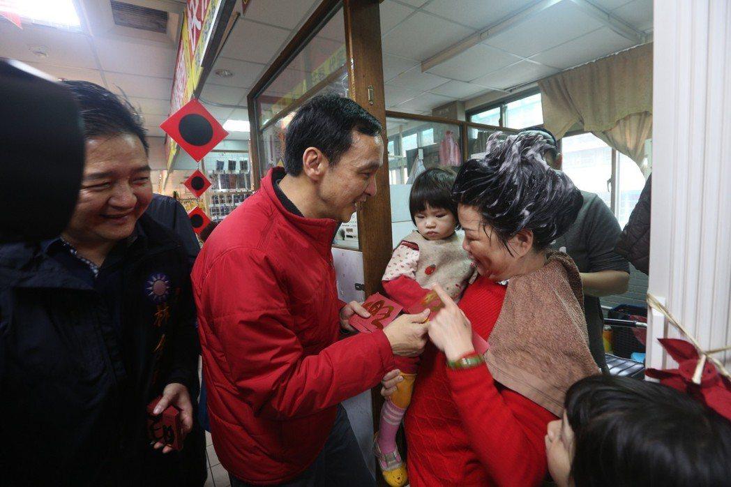 新北市長朱立倫昨天到三峽公有市場發放福袋,一位正在美容院洗頭的太太連忙抱小孩來領...