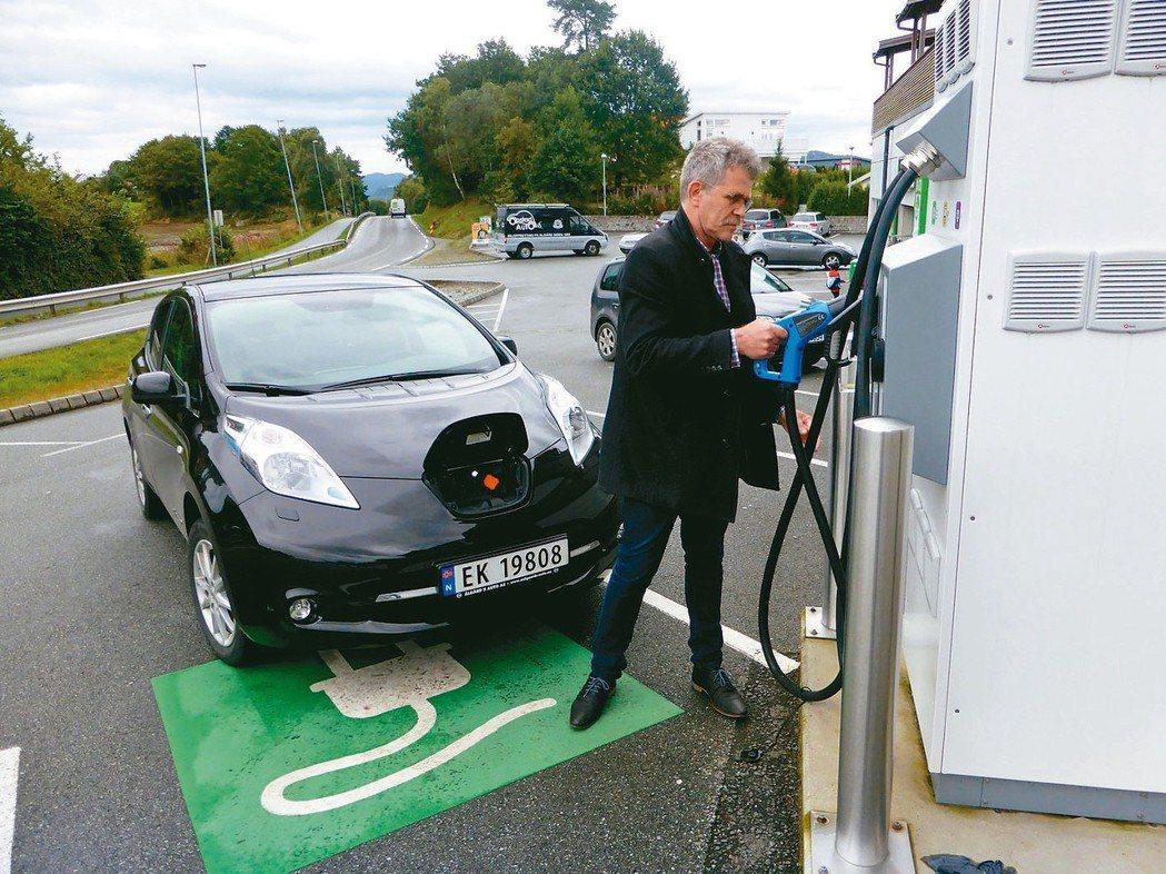 挪威一名車主正在為他的日產Leaf電動車充電。 路透