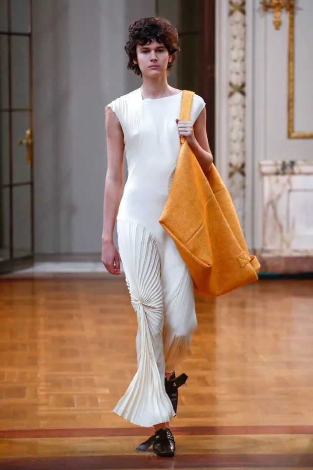 不對稱的連身百褶褲裝、上寬下窄的貼身洋裝搭配百褶長裙,飄逸有型,用寬與窄的融合,...