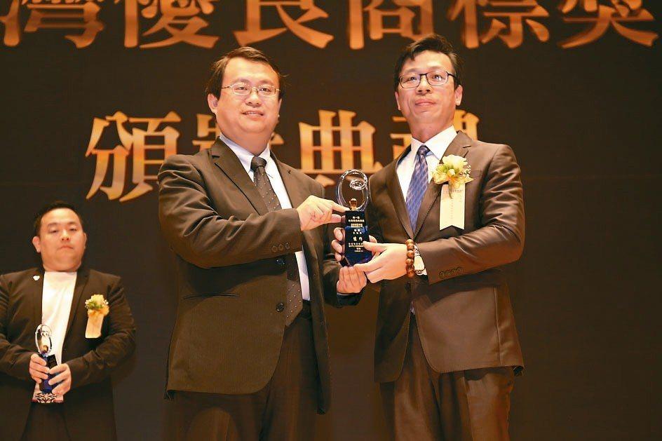 旭泰公司董事長王政榮(右)從臺中市經發局局長呂曜志手中接獲獎座。 黃奇鐘/攝影