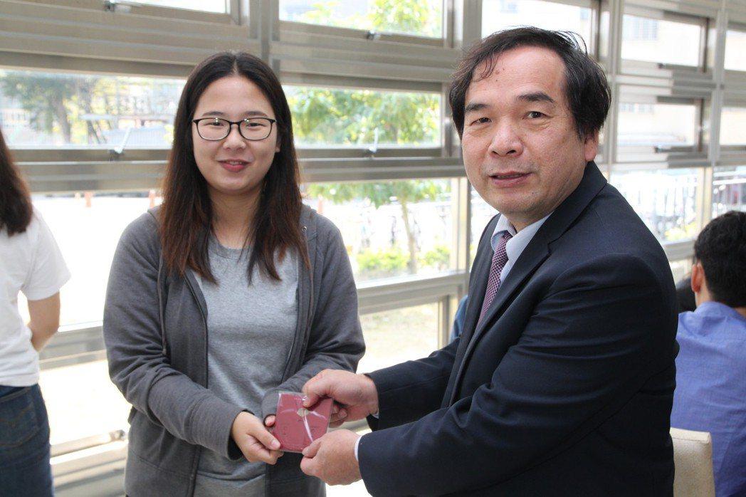 國立勤益科技大學校長陳文淵(右)送紅包給在該校留學的百位外籍生,讓他們體驗中國式...