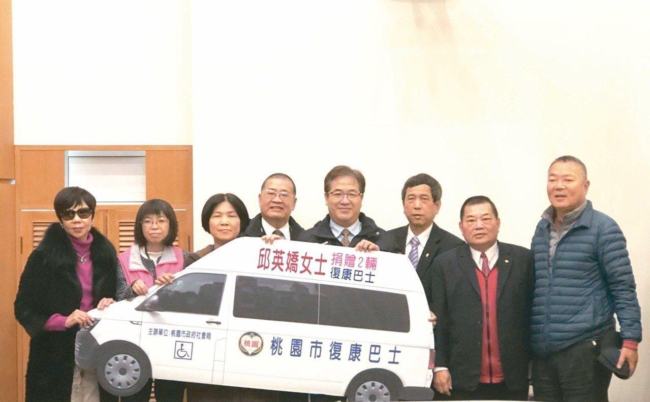 邱英嬌的二姊邱春女(左3)昨天以妹妹名義,代為捐贈兩輛復康巴士,副市長游建華(右...