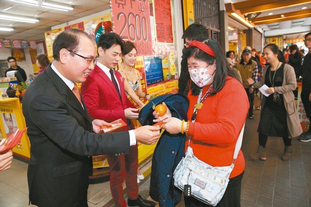 台彩總經理蔡國基(左)上午向民眾拜早年、發大樂透紅包。 記者曾吉松/攝影