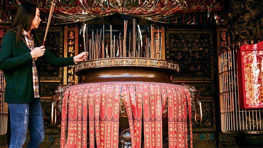 一樓「媽祖爐」上總貼滿各地宮廟前來進香的紅色貼條,可見信徒遍布全台。(攝影者.石...
