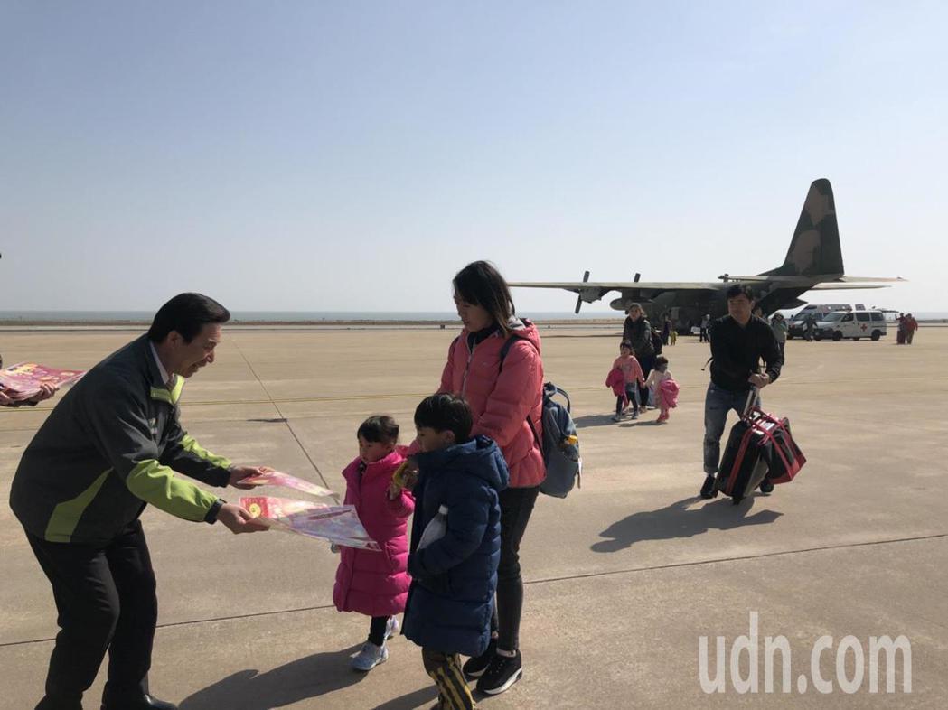 金門縣長陳福海(左1)昨到金門軍用機場迎接返鄉過年的鄉親,並親切的分送小紀念品,...