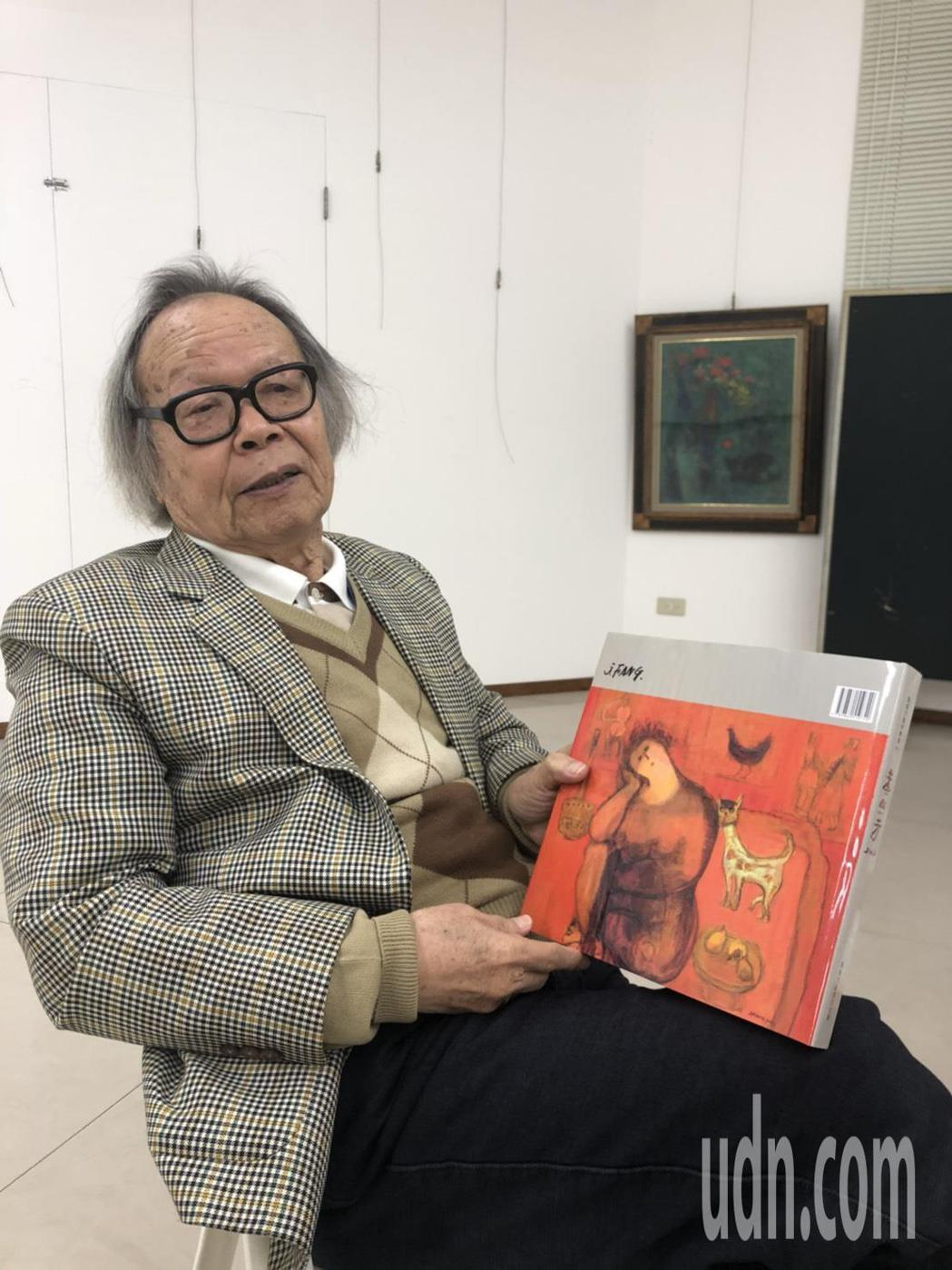 黃照芳老師拿著個展畫冊,訴說人生故事。記者唐秀麗/攝影