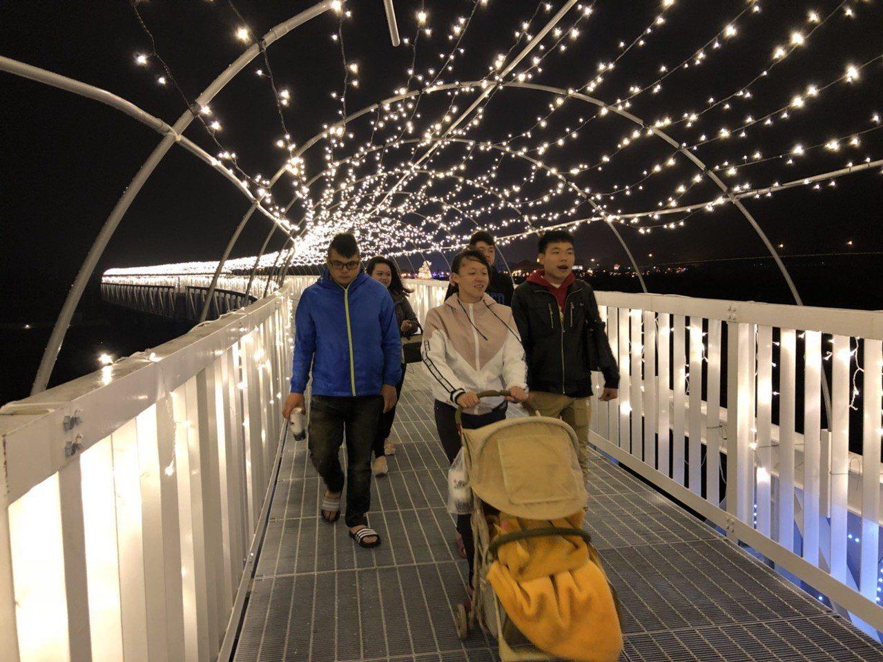 貓羅溪人行橋因為S型設計,夜間開燈化身為白色光橋,吸引民眾感受浪漫氣氛。記者江良...