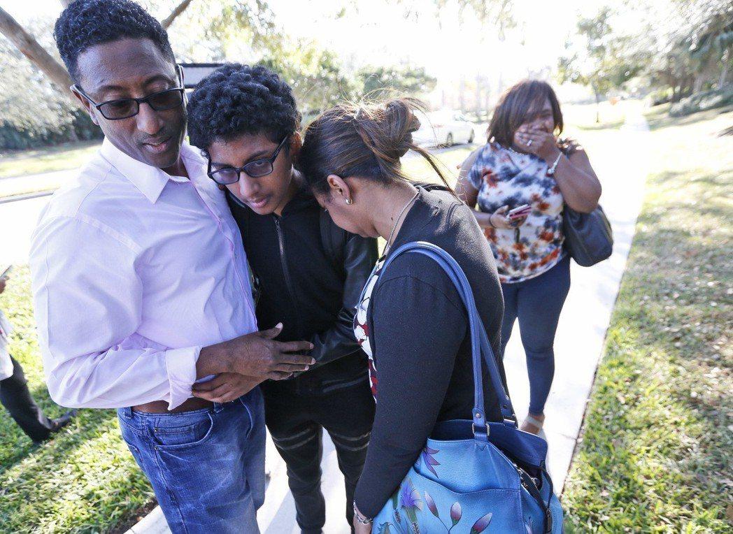 佛州一所高中於14日下午傳出槍響。圖為學生撤出校門後,家長擁抱自己的小孩。美聯社