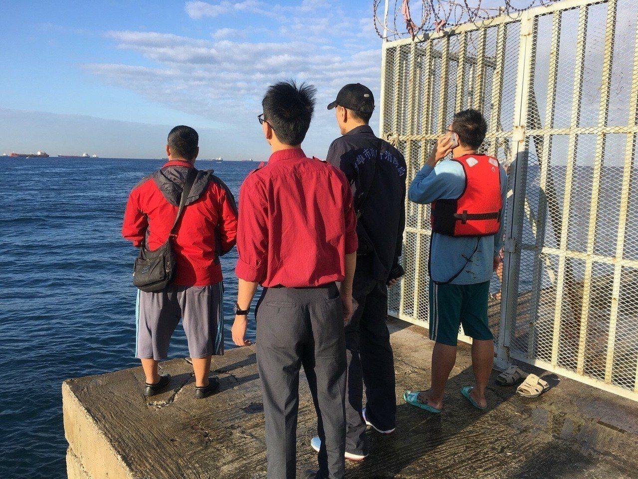 游上岸的周男(右一)與消防人員確認在海上姪子劉姓男的位置。記者劉星君/翻攝