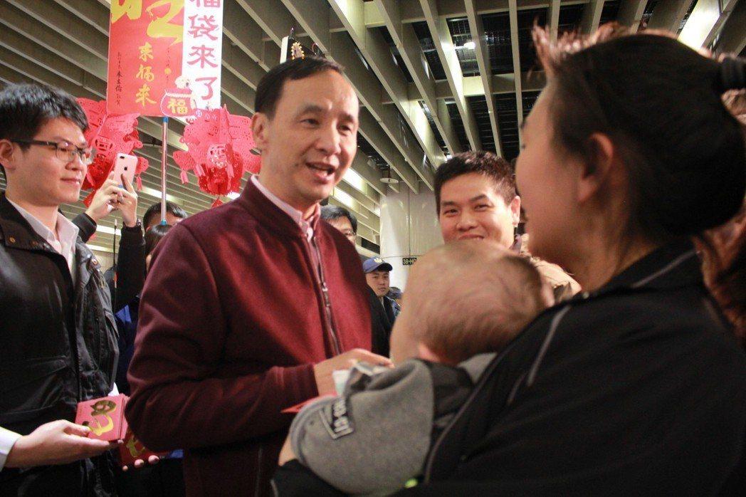 新北市長朱立倫(左二)14日晚間在板橋車站發放福袋給返鄉民眾,受到熱烈歡迎。記者...