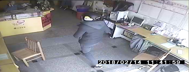 胡姓少年頭戴安全帽、口罩進入彩券行的身影。圖/翻攝自監視器影像