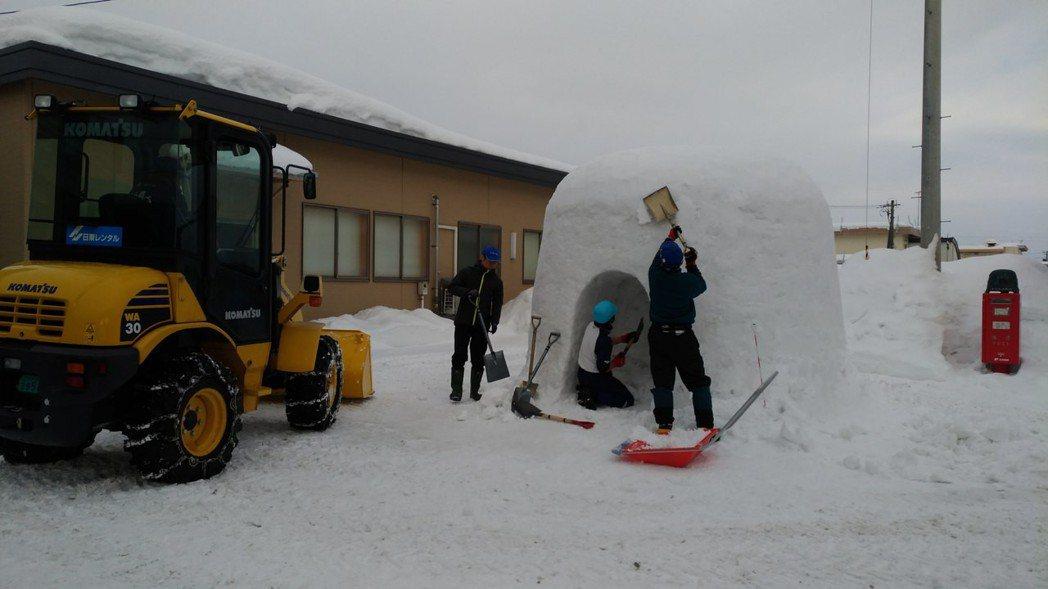 工作人員於活動前幾天,在JR横手車站外就搭建起雪屋,不只數名人力執鏟,還有出動機...