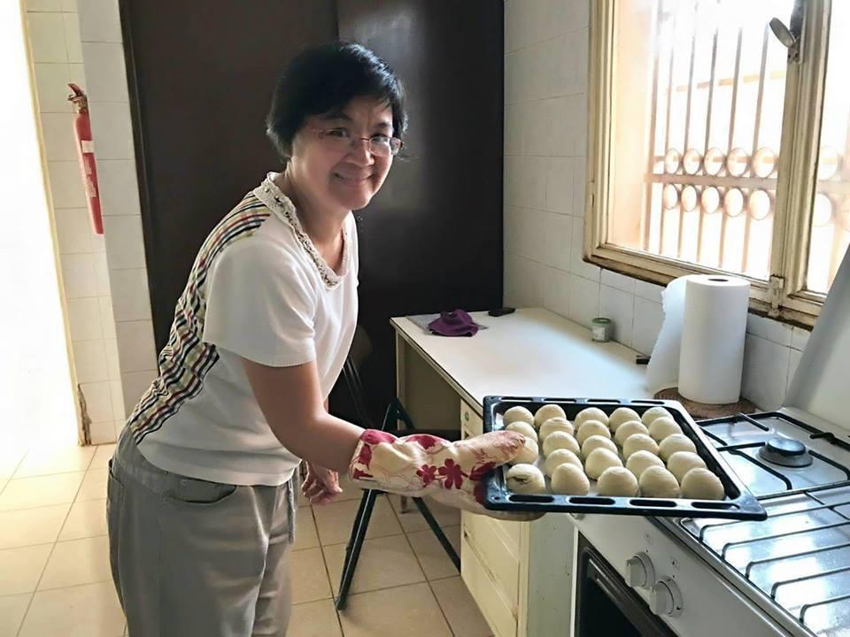 林秀穗準備將蛋黃酥送進烤箱。圖/布吉納法索大使館提供